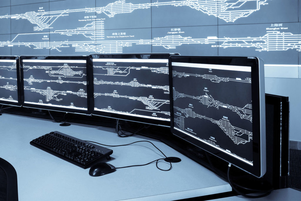 Computer screens in a control room showing diagrams of train lines
