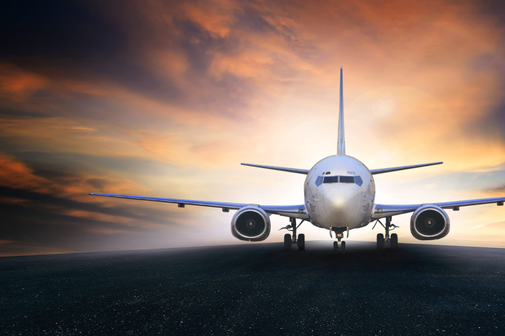 Front view of a passenger aircraft on a runway with a sunset